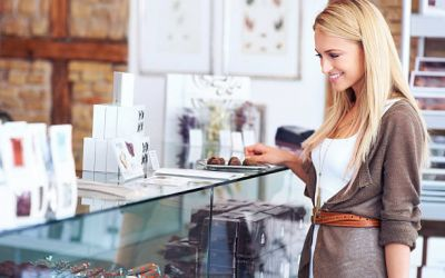 Pretty woman in a shop looking at a delicious display - Copyspace